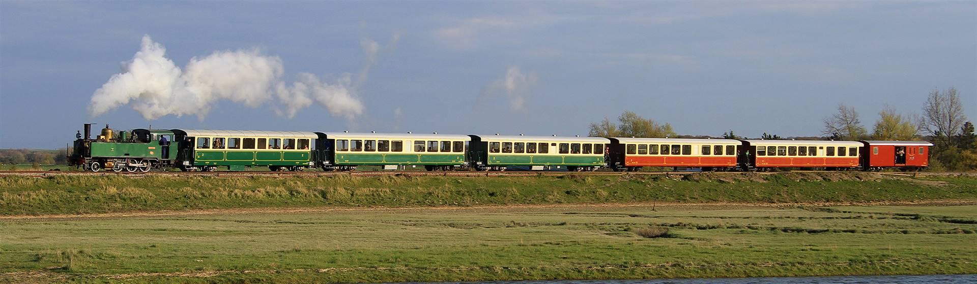 "<img src=""baiedesommepassengerandlake.jpeg"" alt=""Baie De Somme Passenger Train""/>"